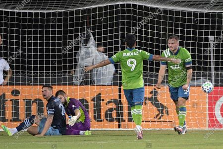 Seattle Sounders forward Jordan Morris, right, celebrates after scoring a goal past Vancouver Whitecaps defender Jake Nerwinski, left, and goalkeeper Maxime Crepeau during the first half of an MLS soccer match, in Kissimmee, Fla. Coming to congratulate Morris is Sounders forward Raul Ruidiaz (9
