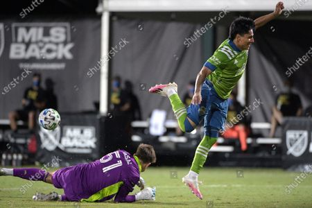 Seattle Sounders forward Raul Ruidiaz (9) goes airborne after having his shot blocked by Vancouver Whitecaps goalkeeper Thomas Hasal (51) during the second half of an MLS soccer match, in Kissimmee, Fla