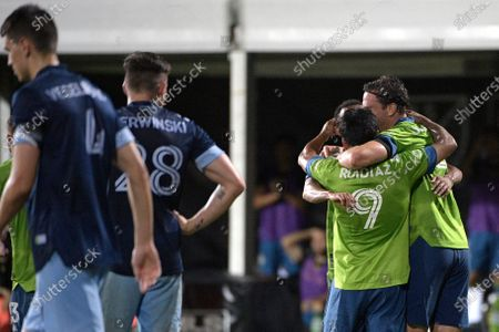 Seattle Sounders forward Raul Ruidiaz (9) is congratulated by teammates, as Vancouver Whitecaps defender Jake Nerwinski (28) watches, after scoring a goal during the second half of an MLS soccer match, in Kissimmee, Fla