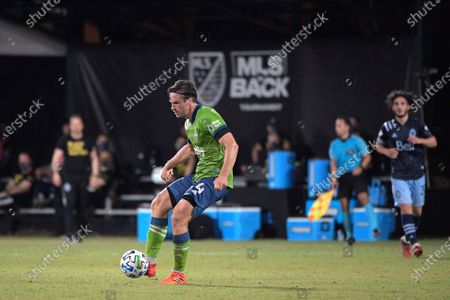 Seattle Sounders defender Gustav Svensson (4) passes a ball in front of Vancouver Whitecaps midfielder Russell Teibert (31) during the second half of an MLS soccer match, in Kissimmee, Fla
