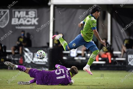 Seattle Sounders forward Raul Ruidiaz, right, goes airborne after having his shot blocked by Vancouver Whitecaps goalkeeper Thomas Hasal (51) during the second half of an MLS soccer match, in Kissimmee, Fla