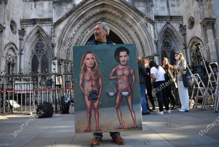 Satirical artist Kaya Mar poses with a painting depicting US actress Amber Heard and her former husband and US actor Johnny Depp at the Royal Courts of Justice in London, Britain, 20 July 2020. Depp is suing The Sun's newspaper publisher News Group Newspapers (NGN) over claims he abused his ex-wife, US actress Amber Heard.
