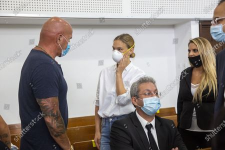 Israeli top model Bar Refaeli, center, wearing a face mask arrives to a court along with her father, Raffi, left, and lawyers, in Tel Aviv, Israel, . Refaeli signed a plea bargain agreement with authorities to settle a long-standing tax evasion case against her and her family. The deal will require Refaeli to serve nine months of community service while her mother, Zipi, will be sent to prison for 16 months. The two are also ordered to pay a $1.5 million fine on top of millions of back taxes owed to the state