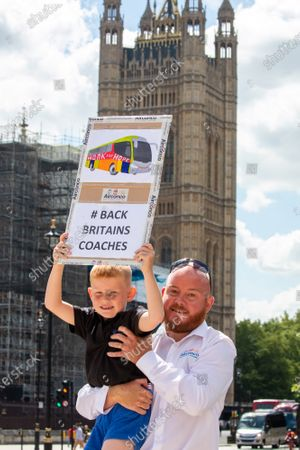 Stock Photo of Justin Scott and his son Harry 6 from Manchester hold a placard during a coach demonstration in Parliament Square. The demonstration by 500 coaches took place in Westminster including driving around Parliament Square asking government for more help for the coach industry. Last week, Prime Minister Boris Johnson urged Britons to return back to working in offices to help service industries and the economic recovery.