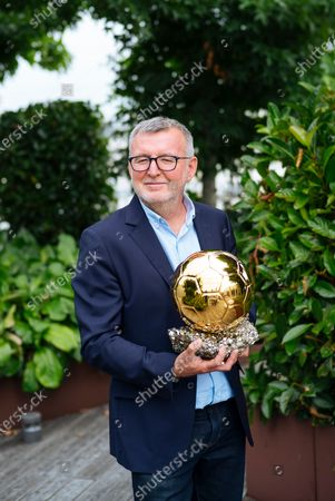 France Football magazine chief editor Pascal Ferre holds the Ballon d'Or award during an interview with The Associated Press in Boulogne-Billancourt, outside Paris, . The prestigious Ballon d'Or will not be awarded this year because the coronavirus pandemic has disrupted the soccer season. Awarded by France Football magazine, the Ballon d'Or has been given out every year since Stanley Matthews won the first one in 1956. Lionel Messi has won it a record six times - one more than longtime rival Cristiano Ronaldo