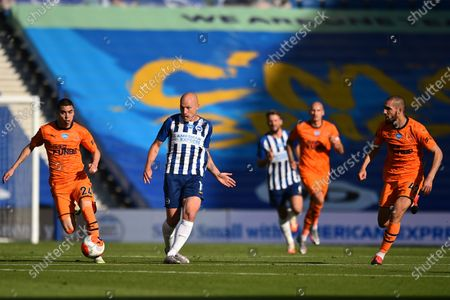 Brighton's Aaron Mooy, center, plays the ball between Newcastle's Nabil Bentaleb, right, and Newcastle's Miguel Almiron during the English Premier League soccer match between Brighton and Newcastle United at the American Express Community Stadium in Brighton, England