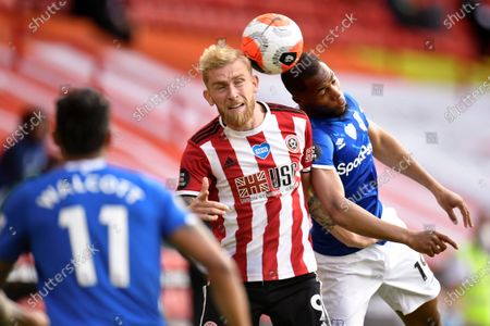 Stock Photo of Sheffield United's Oliver McBurnie, center, goes up for the ball against Everton's Djibril Sidibe, right, during the English Premier League soccer match between Sheffield United and Everton at Bramall Lane in Sheffield, England, . Everton's Theo Walcott (11) looks on during the play