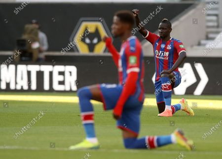Crystal Palace's Mamadou Sakho, right, gestures for Black Lives Matter ahead of the English Premier League soccer match between Wolverhampton Wanderers and Crystal Palace at Molineux Stadium in Wolverhampton, England