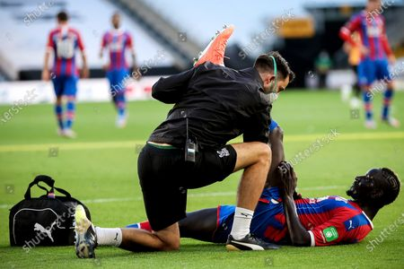 Crystal Palace's Mamadou Sakho (R) gets medical assistance during the English Premier League soccer match between Wolverhampton Wanderers and Crystal Palace in Wolverhampton, Britain, 20 July 2020.