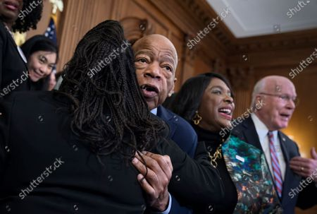 """Civil rights leader Rep. John Lewis, D-Ga., is hugged as House Democrats gathered before passing the Voting Rights Advancement Act to eliminate potential state and local voter suppression laws, at the Capitol in Washington. At right is Rep. Terri Sewell, D-Ala., who introduced the bill and who represents Selma, Ala., a city that was at the forefront of the 1960s civil rights movement. They are joined at far right by Sen. Patrick Leahy, D-Vt. Mourning the death of civil rights hero John Lewis, Democrats are urging the Senate to take up a bill of enduring importance to Lewis throughout his life: protecting and expanding the right to vote. Speaker Nancy Pelosi, Majority Whip Jim Clyburn and other Democrats say the Senate should take up a House-passed bill to restore key sections of the 1965 Voting Rights Act and rename it for Lewis. Senate Majority Leader Mitch McConnell called Lewis a """"great man"""" who helped bend the nation's history toward justice, but Republicans appear unlikely to bring up the voting rights bill for a Senate vote"""