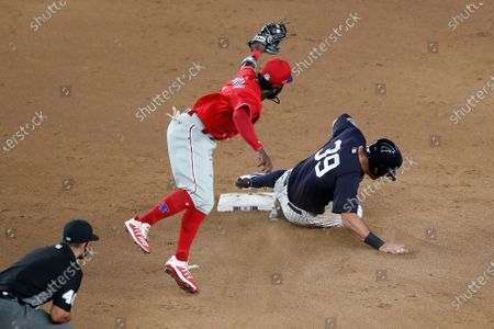 Second base umpire Roberto Ortiz (40) watches as Philadelphia Phillies second baseman Josh Harrison remains airborne after tagging out New York Yankees Mike Tauchman after Tauchman unsuccessfully tried to steal second during the eighth inning of an exhibition baseball game, at Yankee Stadium in New York