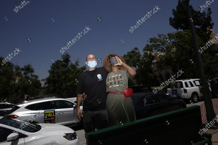 Stock Image of Chris Martinez, right, and her husband, Shaun, attend a rally in Los Angeles, . Thousands across the country walked off the job to protest systemic racism and economic inequality that has worsened during the coronavirus pandemic