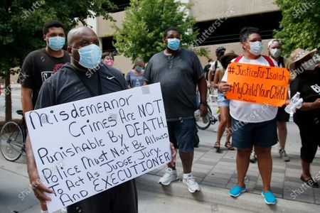 Paul Tramble, left, and Alisha Tramble Jackson, right, an uncle and aunt of Isaiah Lewis, hold signs at a protest, in Oklahoma City. Protestors called for call for Oklahoma County District Attorney David Prater to reopen his investigation into the April 2019 shooting death of 17-year-old Isaiah Mark Lewis by police in the Oklahoma City suburb of Edmond, Okla