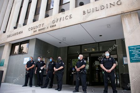 Sheriff's deputies watch protesters outside the Oklahoma County office building, in Oklahoma City. Protestors were calling for Oklahoma County District Attorney David Prater to reopen his investigation into the April 2019 shooting death of 17-year-old Isaiah Mark Lewis by police in the Oklahoma City suburb of Edmond, Okla