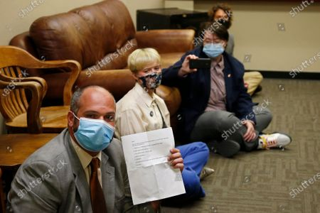 Jess Eddy, left, holds a list of demands as a group of protestors sit-in at the office of Oklahoma County District Attorney David Prater, in Oklahoma City. The demands included a call for Prater to reopen his investigation into the April 2019 shooting death of 17-year-old Isaiah Mark Lewis by police in the Oklahoma City suburb of Edmond, Okla