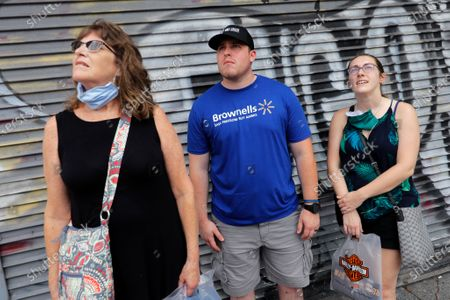 Passers-by Ginger Neel, left, Garrett Neel, and Taylor Neel, of Jamestown, N.Y., watch as a wrecking ball knocks debris loose from the Hard Rock Hotel building collapse site in New Orleans, . New Orleans' fire chief says it's taking longer than expected to remove the bodies of two construction workers from a hotel that partially collapsed during construction 10 months ago. Fire Superintendent Tim McConnell said that the first may be out by the end of this week and the other next week