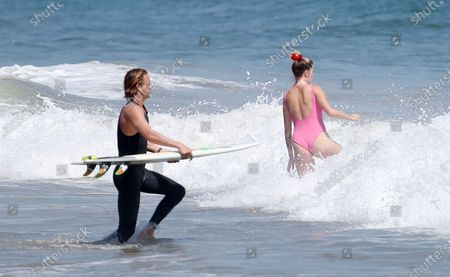 Ireland Baldwin wears a pink one-piece bathing suit while at the beach with her boyfriend Corey Harper