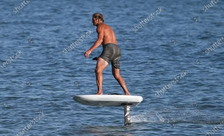 Stock Image of Laird Hamilton rides a electric hydrofoil surfboard in Malibu