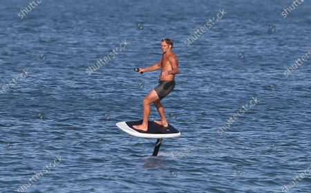 Stock Photo of Laird Hamilton rides a electric hydrofoil surfboard in Malibu