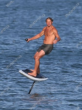 Stock Picture of Laird Hamilton rides a electric hydrofoil surfboard in Malibu