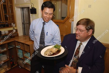 Evening Standard Food Critic Charles Campion Is Served By David Lam Koi Carp Cooked In Ginger And Spring Onion At The Fung Shing Restaurant In Chinatown. London
