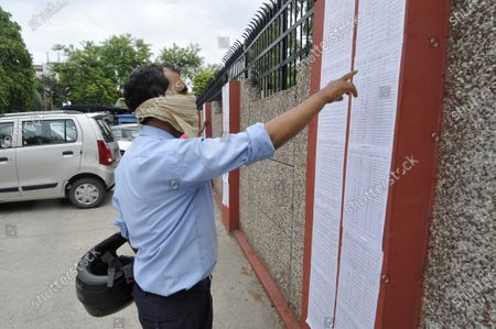 Applicants check for their names in the list allottees for flats built in Sector 123 outside the Indira Gandhi Kala Kendra in Sector 6, on July 20, 2020 in Noida, India.