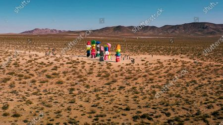 Stock Photo of Visitors are dwarfed by brightly coloured sculptures comprising of stones that punctuate the stark, dry landscape of the Mojave desert in Nevada, USA.   The unusual but striking shots were taken by Las Vegas native Henry Do, and are located 30 minutes from the main strip. The 7 columns form the outdoor installation, entitled 'Seven Magic Mountains' constructed by artist Ugo Rondinone.
