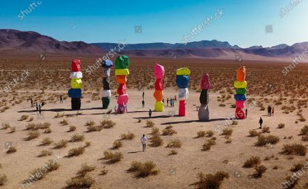 Stock Picture of Visitors are dwarfed by brightly coloured sculptures comprising of stones that punctuate the stark, dry landscape of the Mojave desert in Nevada, USA.   The unusual but striking shots were taken by Las Vegas native Henry Do, and are located 30 minutes from the main strip. The 7 columns form the outdoor installation, entitled 'Seven Magic Mountains' constructed by artist Ugo Rondinone.
