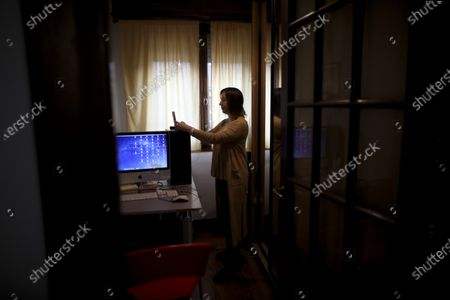 Psychologist Maria Clara Benitez text messages in the room where she attends patients online at her home during a government-ordered lockdown to curb the spread of the new coronavirus in Buenos Aires, Argentina, . In the age of coronavirus, quarantine is posing a special challenge for residents of the world's most analyzed city