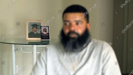 """Just not having my sister around no more, it's going to be a tough one,"""" says Roland Mack during an interview at home in District Heights, Md.,, in front of photos of his sister, Chantee Mack, who died of COVID-19"""