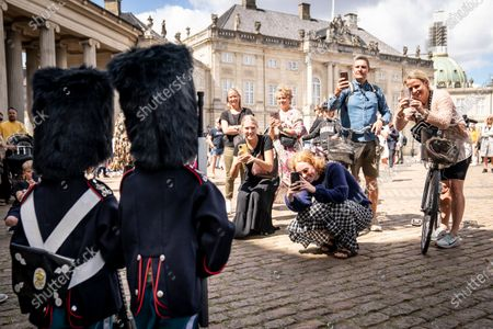 People take photos of the 9-year old twin Malthe and William as they patrol around Amalienborg in Copenhagen, Denmakr, 21 July 2020. The twin likes to dress as the Danish Queen Margrethe's Royal Life Guards amusing visiting tourists and locals.