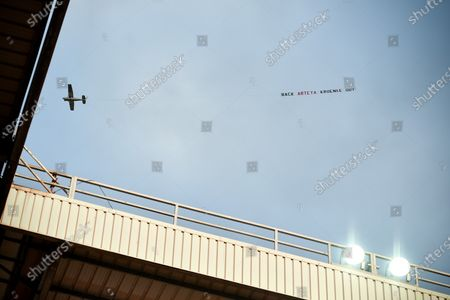 An airplane pulling a banner reading 'Back Arteta, Kroenke out!' making reference to Arsenal's head coach Mikel Arteta and US billionaire and Arsenal's owner Stan Kroenke, during the English Premier League soccer match between Aston Villa and Arsenal London in Birmingham, Britain, 21 July 2020.