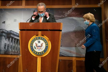 Senate Minority Leader Sen. Chuck Schumer of N.Y., adjusts his facemask as he and Sen. Debbie Stabenow, D-Wis., arrive for a news conference on Capitol Hill in Washington