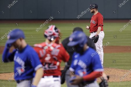 Boston Red Sox relief pitcher Ryan Brasier, top right, waits on the mound after giving up a two-run home run to Toronto Blue Jays' Derek Fisher, which broke a 6-6 tie, during the ninth inning of an exhibition baseball game against the Boston Red Sox, at Fenway Park in Boston. The Blue Jays defeated the Red Sox 8-6