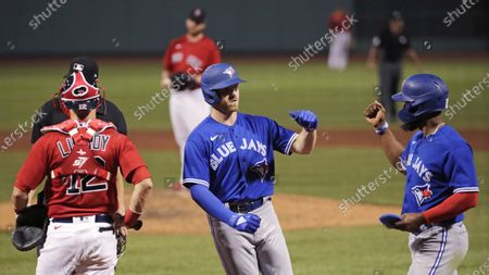Toronto Blue Jays' Derek Fisher, center, is congratulated by Teoscar Hernandez after his two-run home run during the ninth inning of an exhibition baseball game against the Boston Red Sox, at Fenway Park in Boston