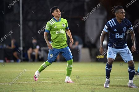 Seattle Sounders forward Raul Ruidiaz (9) and Vancouver Whitecaps forward Yordy Reyna (29) set up for a play during the first half of an MLS soccer match, in Kissimmee, Fla