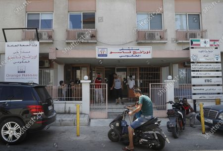 People gather at the entrance of the Orange Nassau Governmental Hospital, in Tripoli, Lebanon, . Just as Lebanon faces a surge in coronavirus cases, hospitals are cracking under the country's financial crisis. The health sector has long been one of the best in the Middle East, with its private hospitals drawing patients from around the region. But with dollars in short supply and the state unable to pay insurance bills, hospitals are having to turn away patients and close wards to cut costs. Public facilities, on the front line of the coronavirus fight, are too underfunded and understaffed to fill the gap