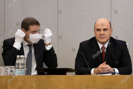 Stock Photo of Russian State Duma deputy speaker Alexander Zhukov, left, takes off his face mask as Russian Prime Minister Mikhail Mishustin sits next prior to a session of the State Duma, the Lower House of the Russian Parliament, with an annual report on the country's economic and social development, in Moscow, Russia, . Russian State Duma speaker Vyacheslav Volodin is seen in the background