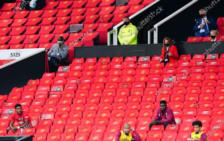 Marcus Rashford sits down, bottom left, after being substituted as former Manchester United manager Sir Alex Ferguson looks on, top right