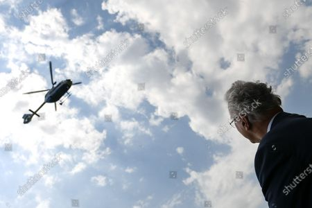 Bavaria's Interior Minister Joachim Herrmann looks on as an H145 helicopter takes off during a press conference at the police headquarters in Munich, Germany, 22 July 2020. Bavaria's police is purchasing eight new Airbus H145 helicopters offering increased payload capacity and overall performance compared to the EC135 model currently in service.