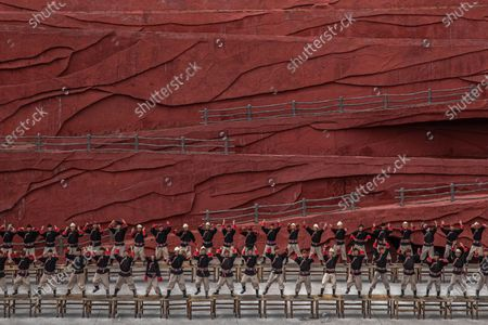 Stock Image of Members of the Naxi, Yi and Bai ethnic minorities perform a cultural show entitled Impression Lijiang with Jade Dragon Snow Mountain as a backdrop, in Lijiang, Yunnan province, China, 15 July 2020 (issued 22 July 2020). Directed by Chinese filmmaker Zhang Yimou, the production aims to present the traditions and the lifestyle of these minorities. Yunnan province is one of the most popular tourist destinations in China, known for its natural scenery, historical and cultural heritage. The tourism industry that was badly affected in China by the Covid-19 pandemic is slowly recovering with more tourists starting to travel around the country. In a survey conducted in May by Boston Consulting Group some 59 percent of the Chinese mainland respondents said they were worried about their finances and traveling.