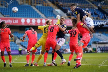 Jake Cooper of Millwall (r) gets above Richard Stearman of Huddersfield Town, and a flailing Huddersfield goalkeeper Joel Coleman to score the second goal