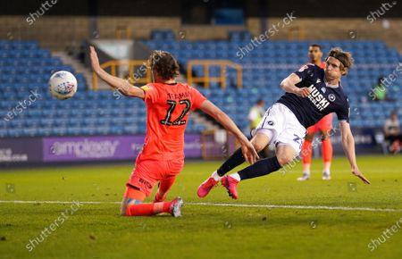Jon Dadi Bodvarsson of Millwall scores the fourth goal past Richard Stearman of Huddersfield Town