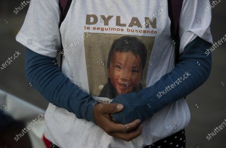 """Juana Perez, whose 2 1/2 year-old son Dylan is missing, wears a T-shirt with his photo and the Spanish phrase: Dylan, we keep looking for you"""" outside of the presidential palace where she hopes to speak with President Manuel Andres Lopez Obrador in Mexico City, . The search for Perez's boy who was led away from a market in southern Mexico's Chiapas state three weeks ago led police to a horrifying discovery: 23 abducted children being kept at a house and forced to sell trinkets in the street. Pérez said officials told her that her son had not yet been found"""