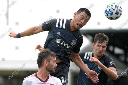 Sporting Kansas City midfielder Roger Espinoza (15) attempts a header on goal in front of midfielder Graham Smith, right, and Real Salt Lake midfielder Kyle Beckerman, front, during the first half of an MLS soccer match, in Kissimmee, Fla