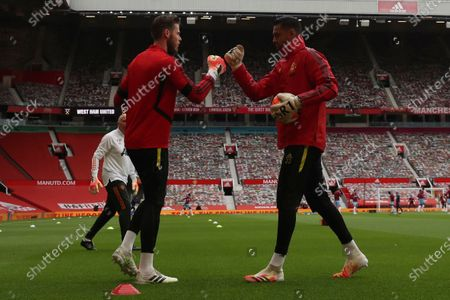 Manchester United's goalkeeper David de Gea, left and Manchester United's goalkeeper Sergio Romero greet each other ahead of the English Premier League soccer match between Manchester United and West Ham at the Old Trafford stadium in Manchester, England