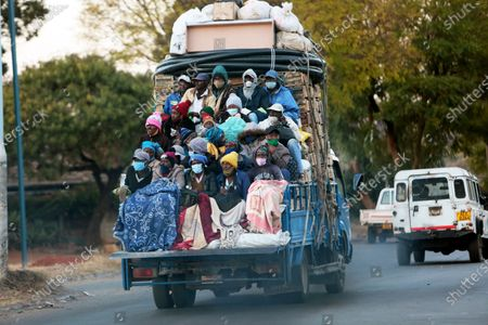 An open truck carries farmers wearing face masks on the first day of the curfew in Harare, . Zimbabwean President Emmerson Mnangagwa announced a dusk to dawn curfew, banned political, religious and social gatherings and reduced business operating hours as part of measures to slow the spread of the coronavirus