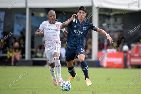 Sporting Kansas City forward Alan Pulido (9) controls a ball in front of Real Salt Lake midfielder Everton Luiz (25) during the first half of an MLS soccer match, in Kissimmee, Fla