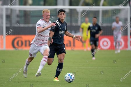 Stock Image of Sporting Kansas City forward Alan Pulido (9) and Real Salt Lake defender Justen Glad (15) compete for a ball during the first half of an MLS soccer match, in Kissimmee, Fla