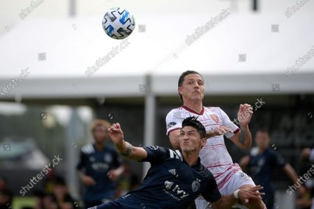 Stock Photo of Sporting Kansas City forward Alan Pulido, left, and Real Salt Lake defender Donny Toia (4) compete for a ball during the first half of an MLS soccer match, in Kissimmee, Fla